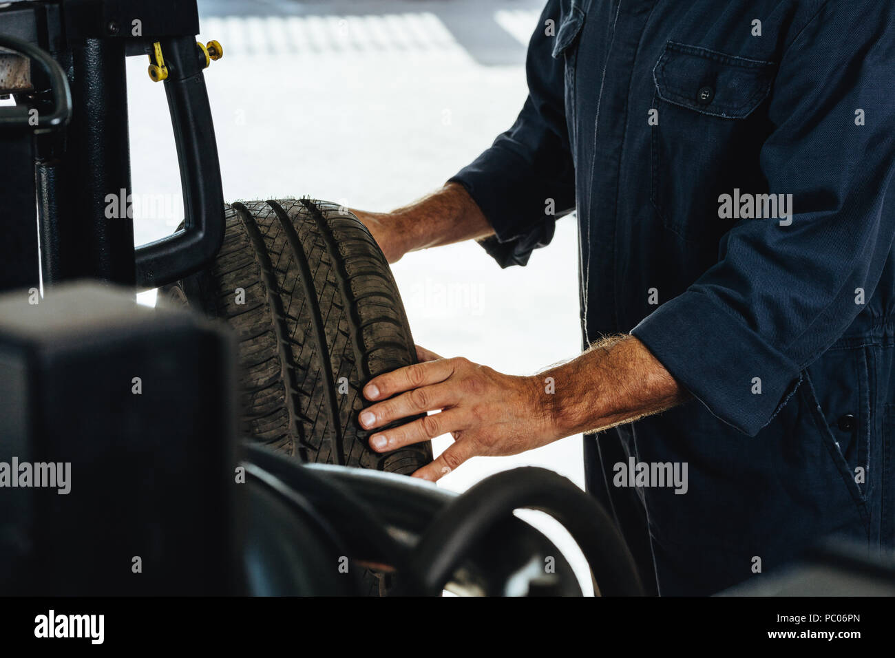 Cropped shot of a mechanic checking the condition of a automobile wheel. Man examining the wear and tear of car tire in garage. - Stock Image