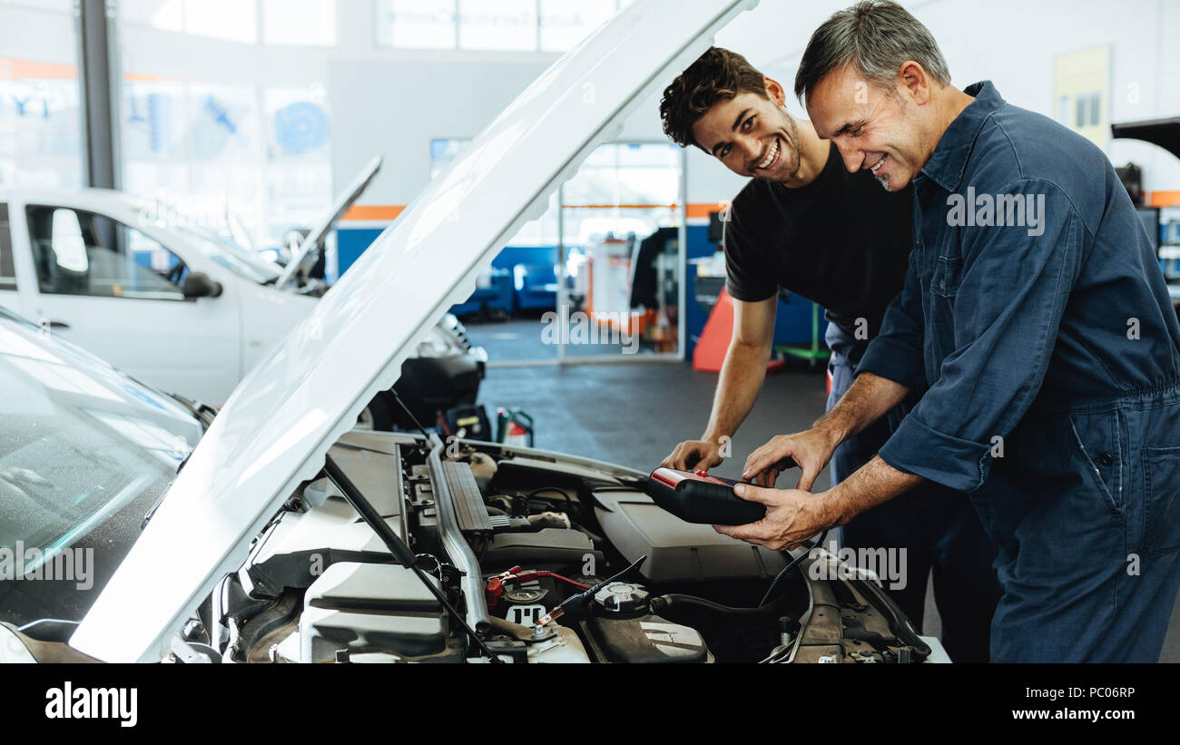 Two happy automobile mechanics doing car engine checkup with a device. Mechanics diagnosing a car in service station. - Stock Image