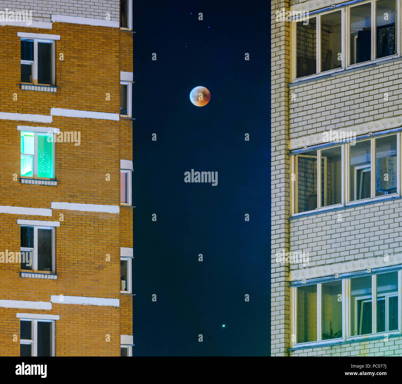 Moon eclipse in full moon. Super blue blood moon in July 27, 2018, Belarus. Cityscape: facade of a multi-storey building against the background of the Stock Photo