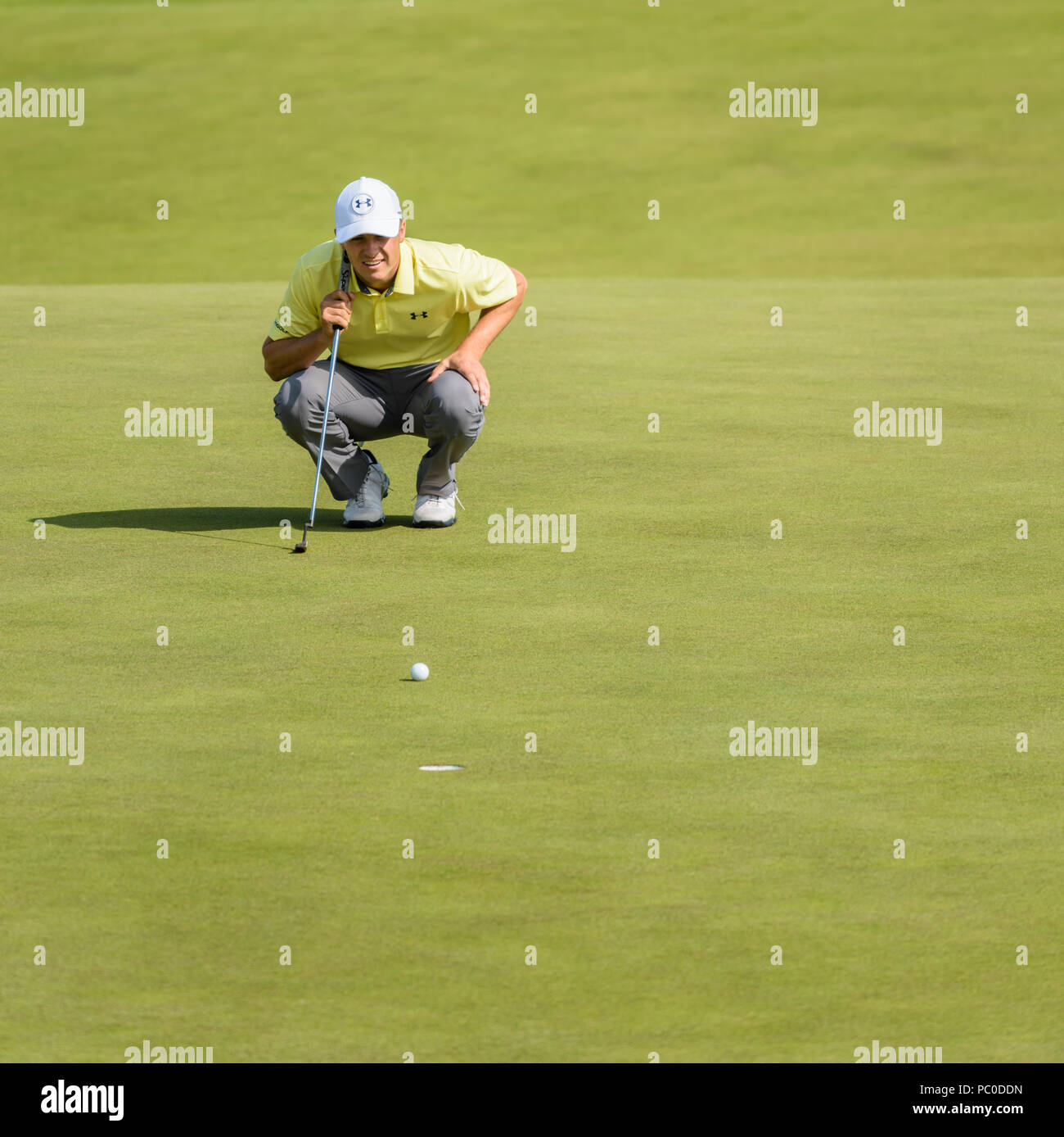 Jordan Spieth showing focus and concentration in lining up a putt on a green at Royal Birkdale, Southport, during a practice day at The Open in 2017 - Stock Image