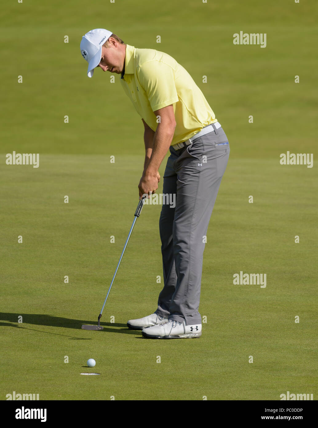 Champion golfer Jordan Spieth showing focus and determination to hole a putt at Royal Birkdale, Southport, during a practice day at The Open in 2017 - Stock Image