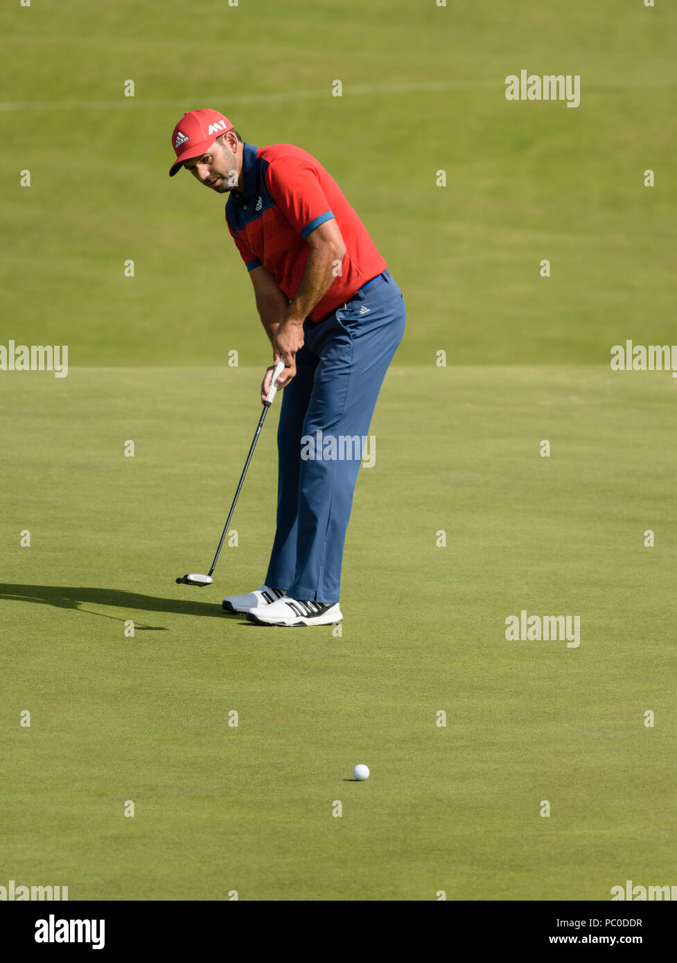 Golfer Sergio Garcia showing focus and determination when putting on a green at Royal Birkdale, Southport, during a practice day at The Open in 2017 - Stock Image
