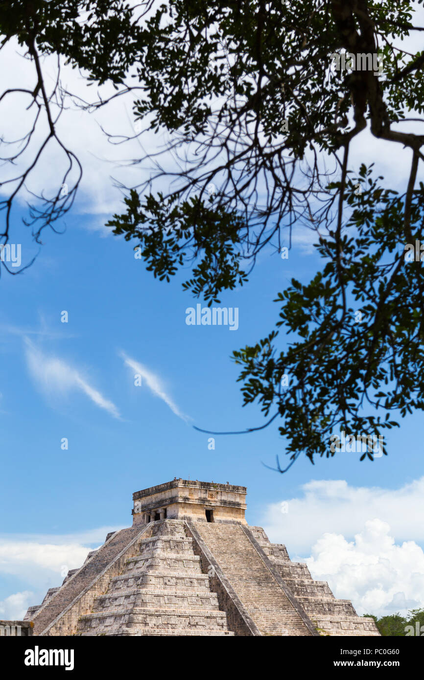 'Temple of Kukulkan (El Castillo)' most famous pyramid at Chichén-Itzá archeological site in the Yucatan peninsula Mexico, framed with tree branches. - Stock Image