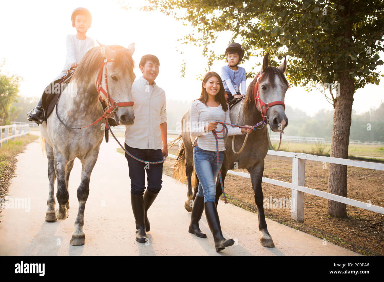 Cheerful young Chinese family riding horses Stock Photo