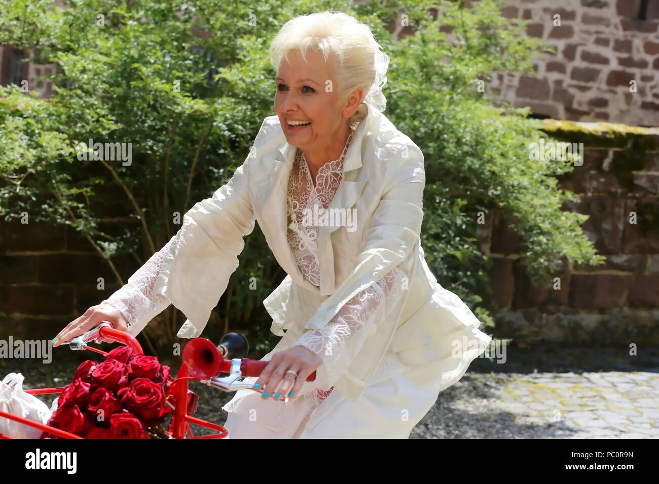 Bride radiant with joy in a romantic designer bridal suit with the red bicycle on the way to the wedding ceremony - Stock Image