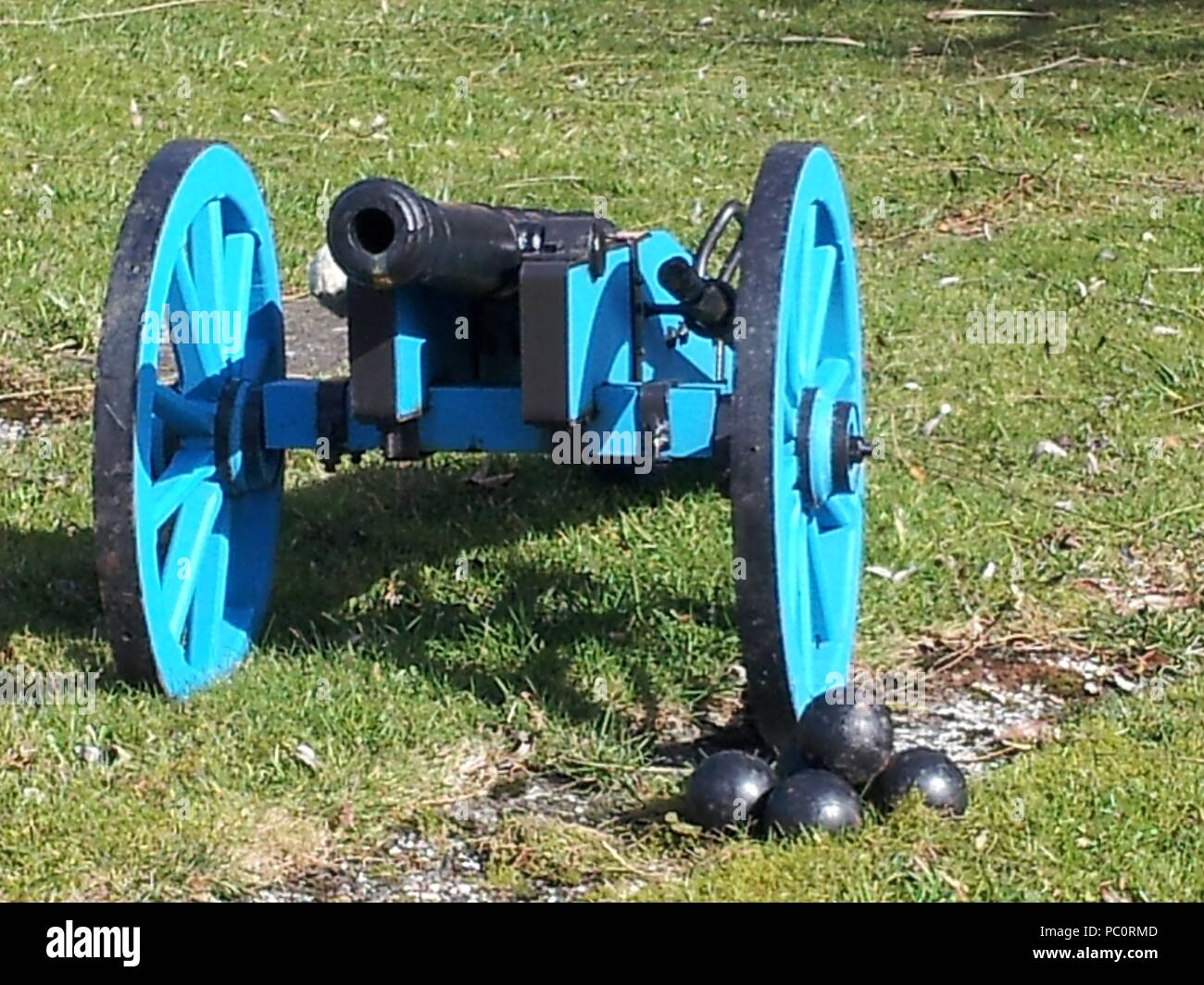 Wooden carriage on wheels with cannon and cannonballs - Stock Image