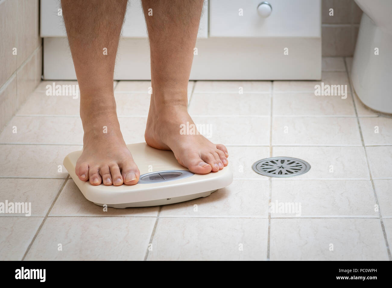 Cropped image of man feet standing on weigh scale, on the bathroom floor - Stock Image
