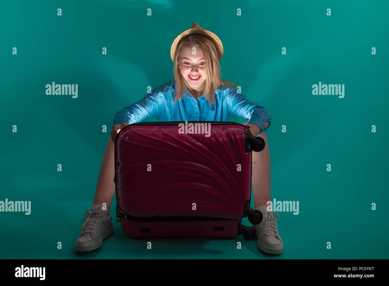 joyful tourist is opening her magic luggage.the light from the baggage.look for outfit at night - Stock Image