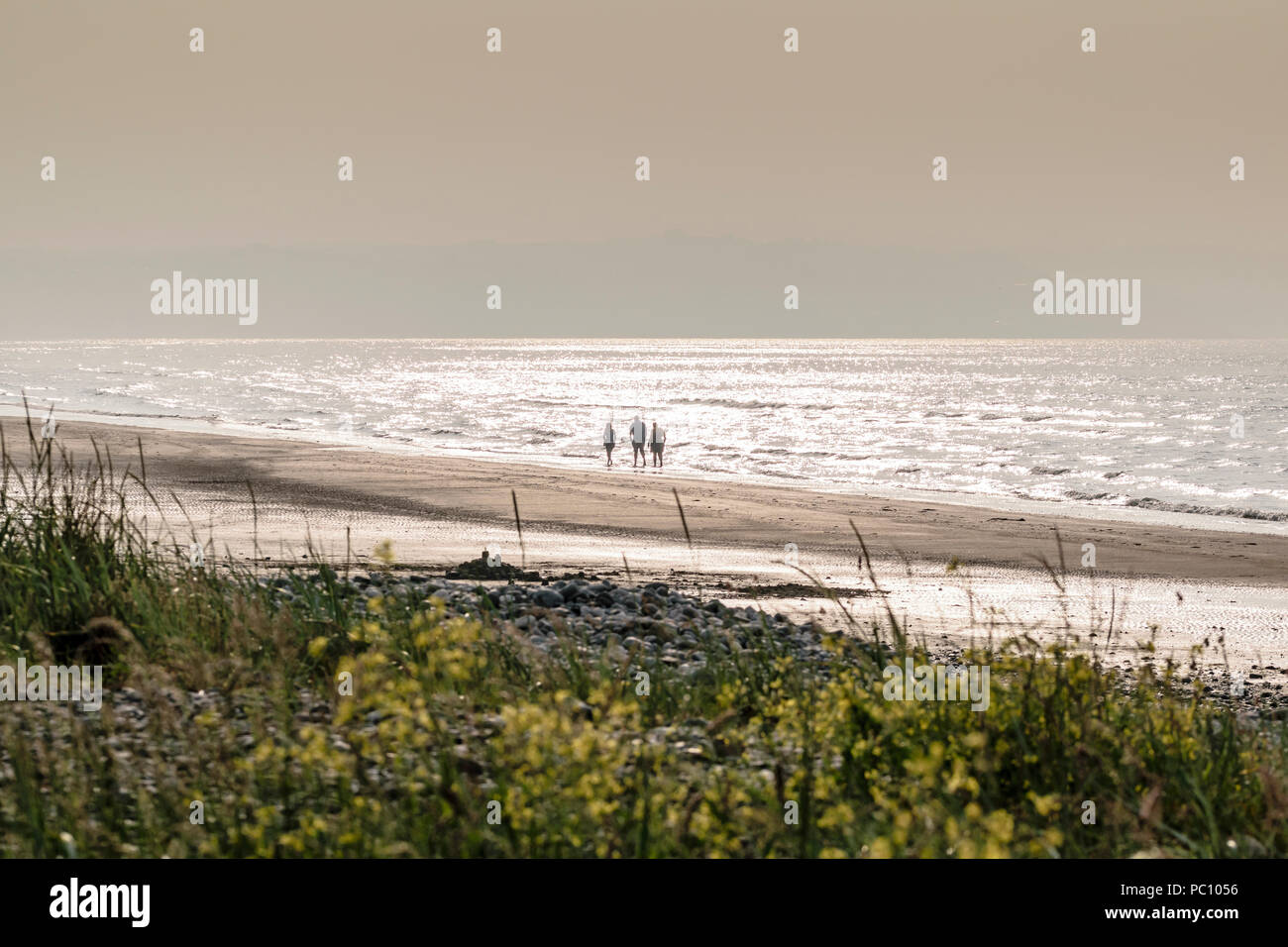 Walkers strolling on the beach at Red Wharf Bay on Anglesey near Llanddona North Wales uk Stock Photo