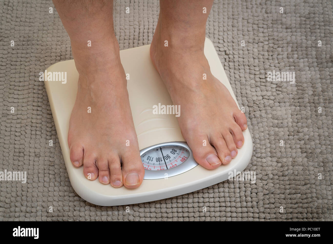 Cropped image of man feet standing on weigh scales, on the bathroom floor - Stock Image