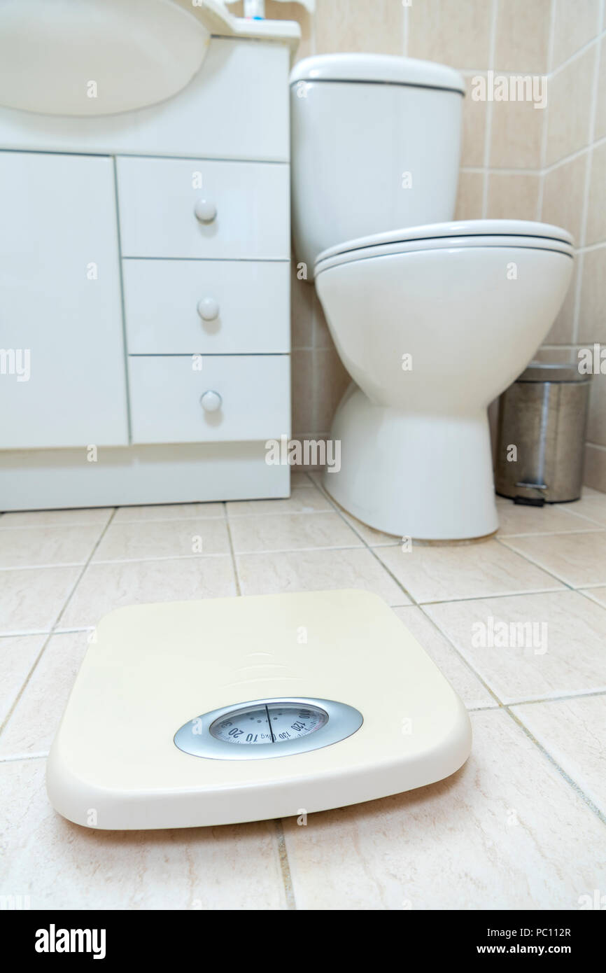 Photo of the bathroom floor with weight scale in the foreground - Stock Image