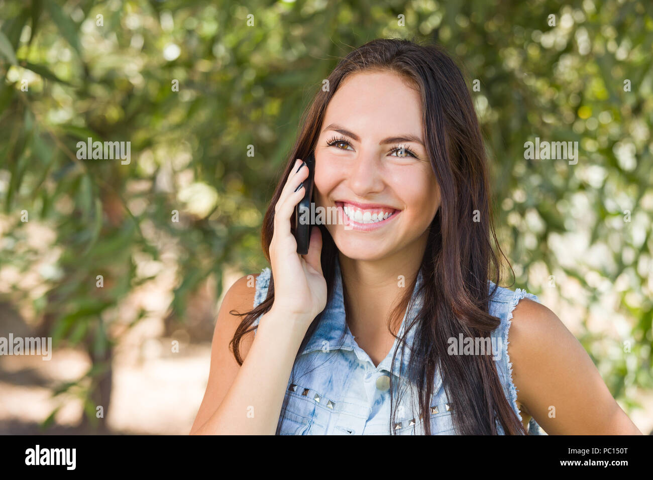 Attractive Happy Mixed Race Young Female Talking On Cell Phone Outside Stock Image