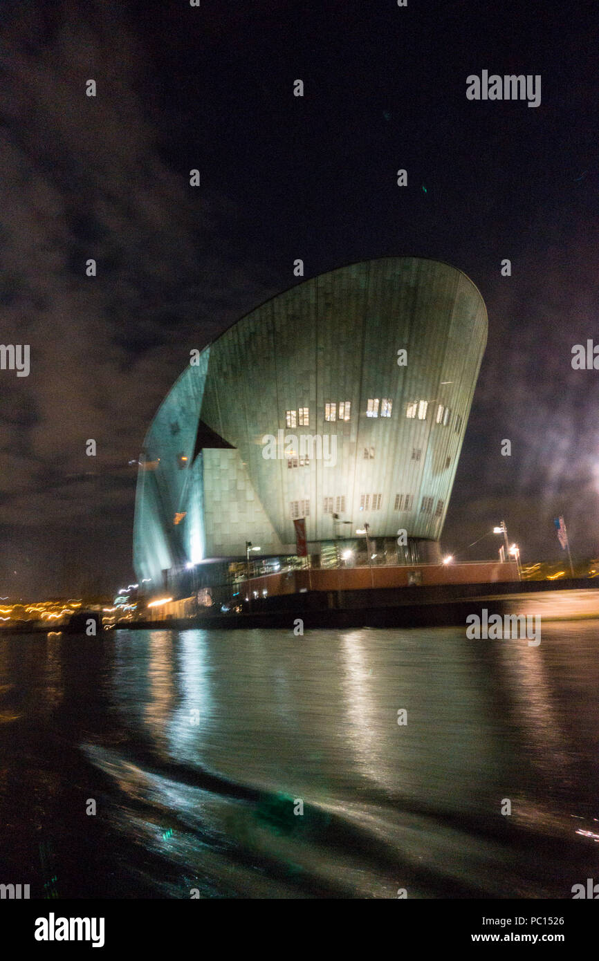 Boat shaped Building on river in Amsterdam - Stock Image
