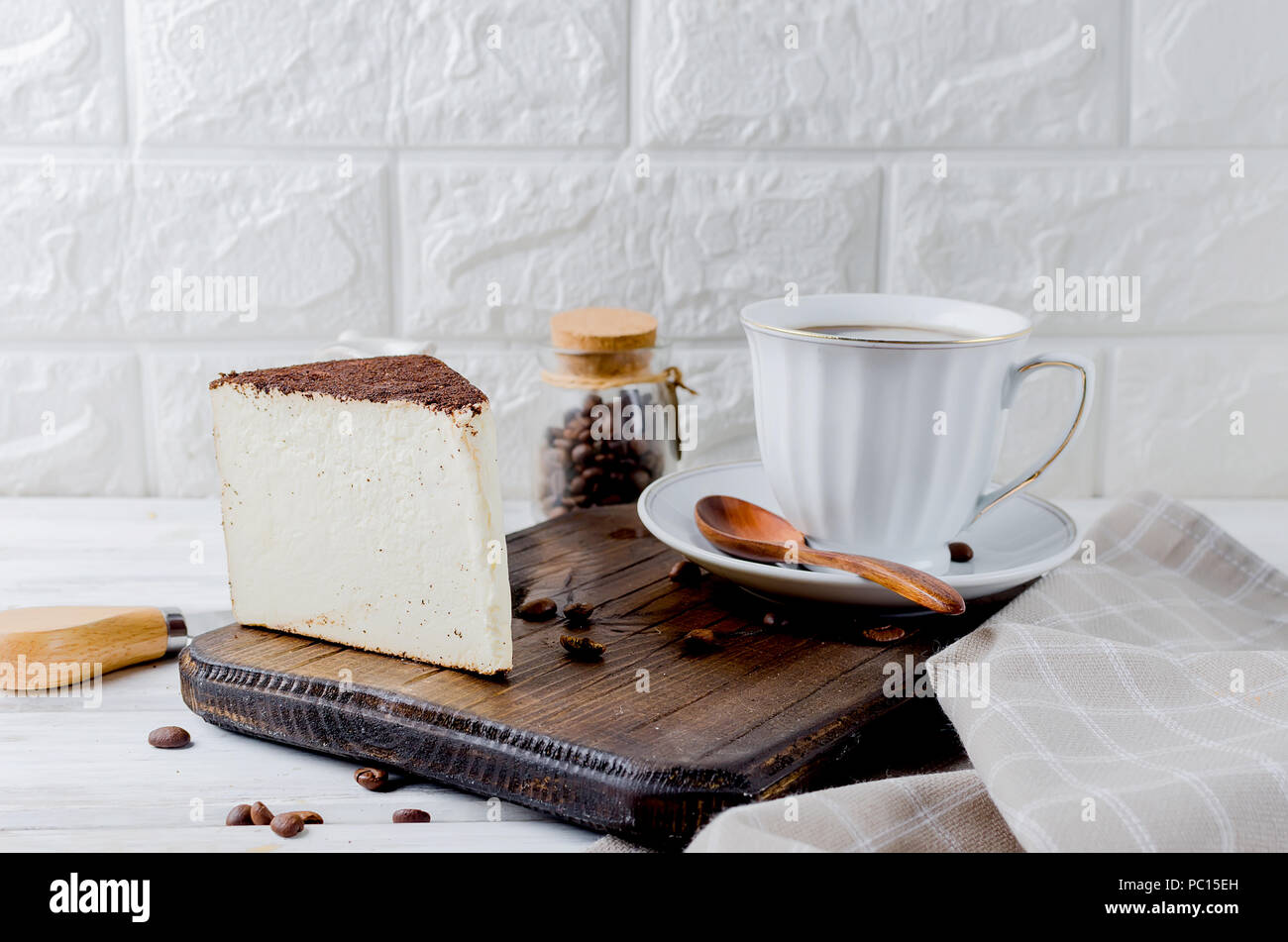 white cup of black coffee with a piece of soft cheese in coffee or cheesecake on old rustic white background,  copy space - Stock Image