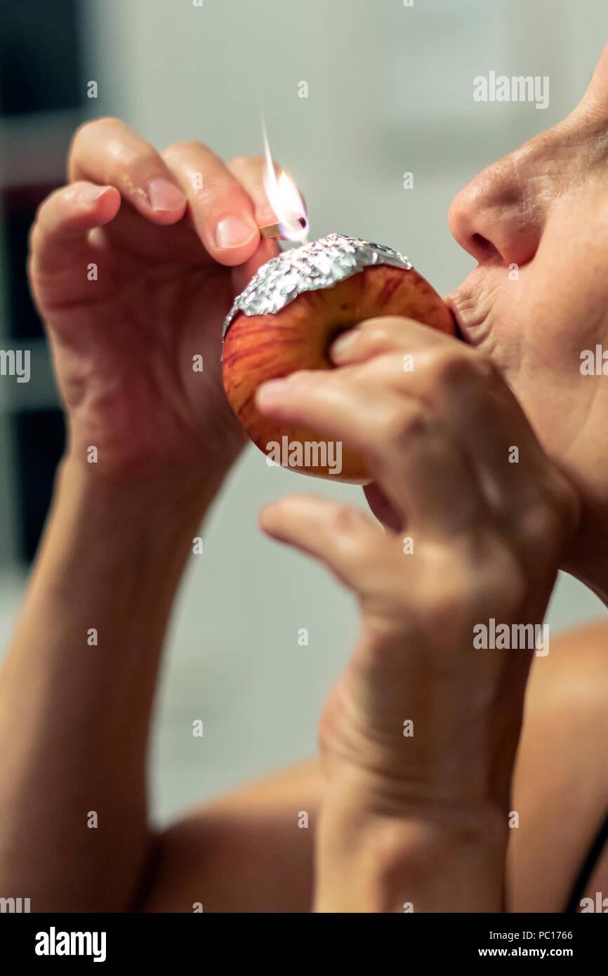 A woman smokes marijuana, using an apple as a pipe. - Stock Image