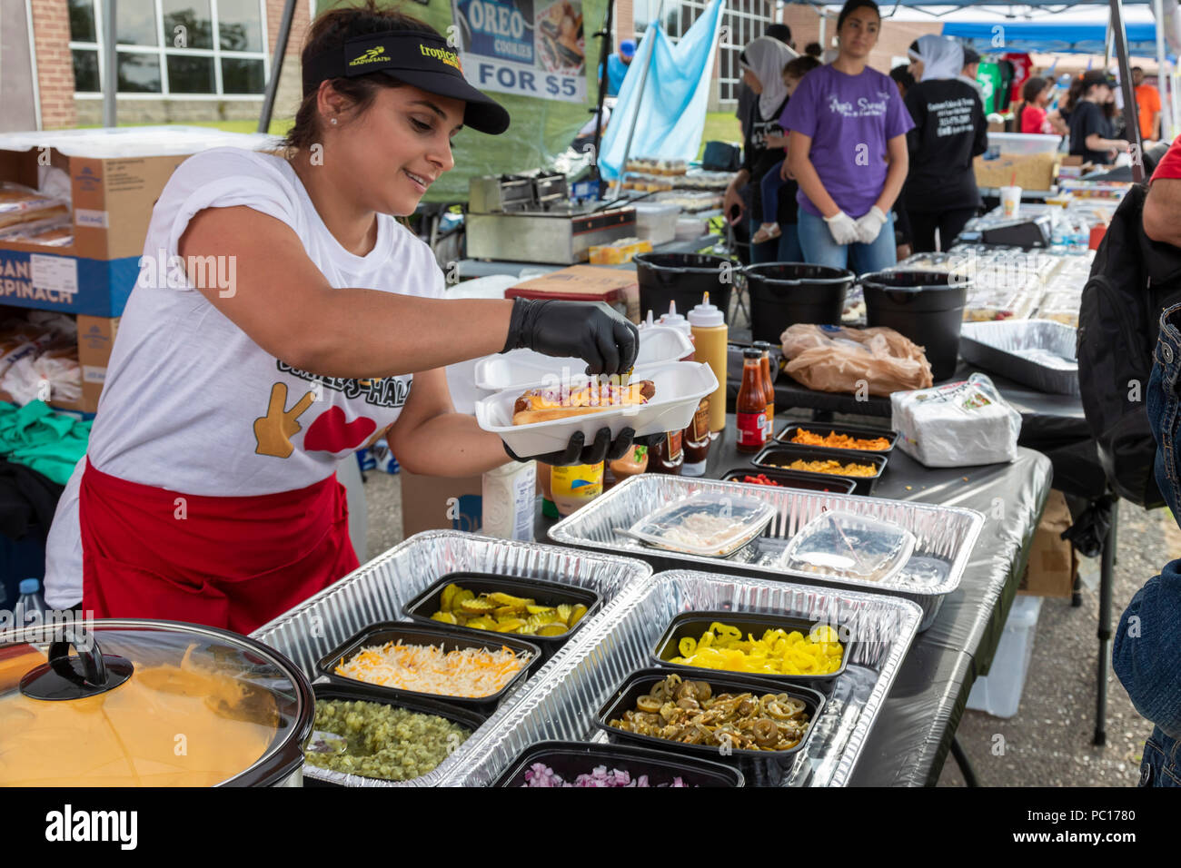 Dearborn, Michigan - A woman adds toppings to a halal hot