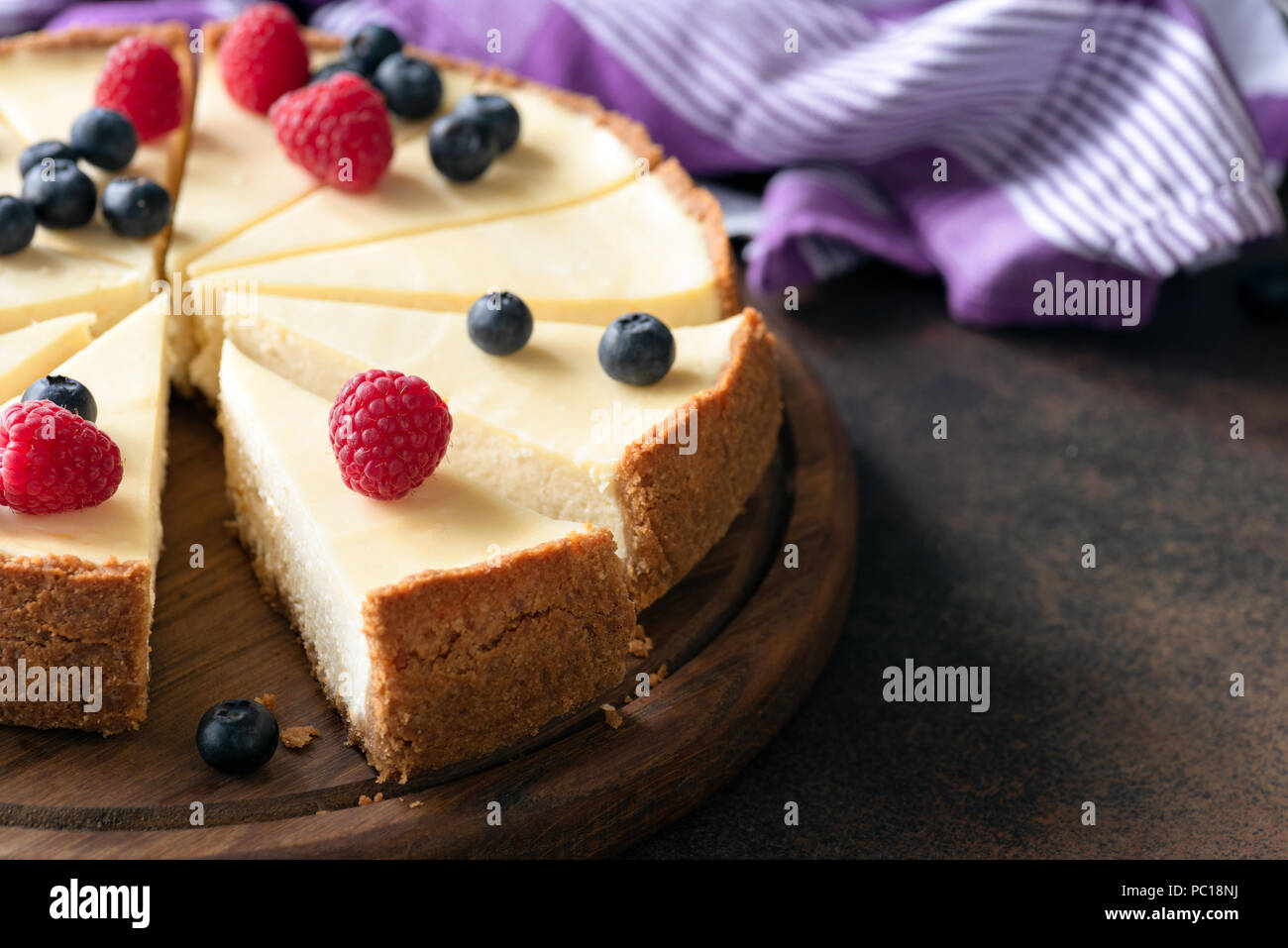 Classic plain New York Cheesecake with fresh berries sliced on wooden board, closeup view, selective focus - Stock Image