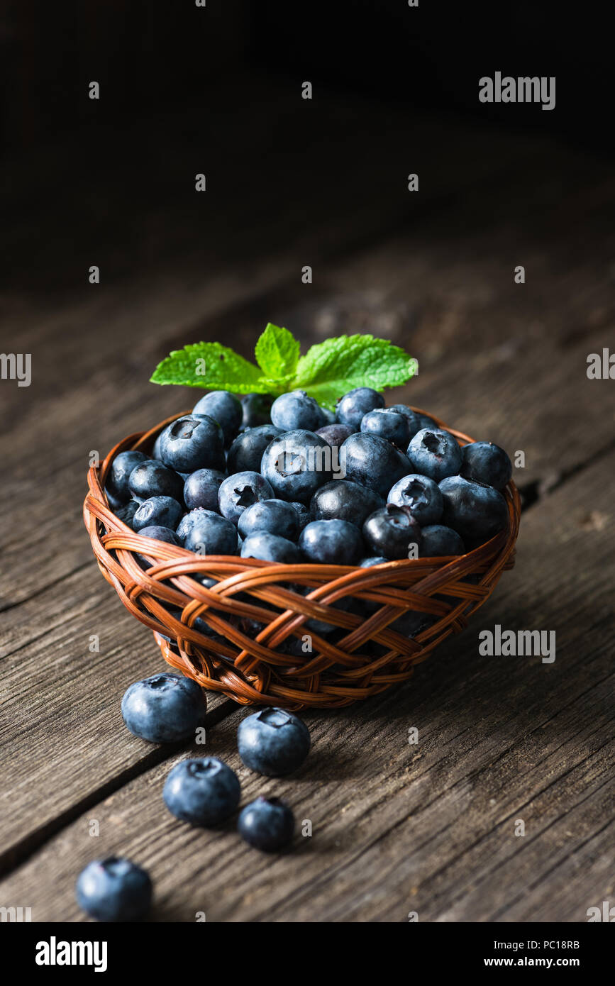 Blueberries in basket on wooden table. Freshly picked blueberries. Low key, dark food photo. Summer harvest. Selective focus Stock Photo