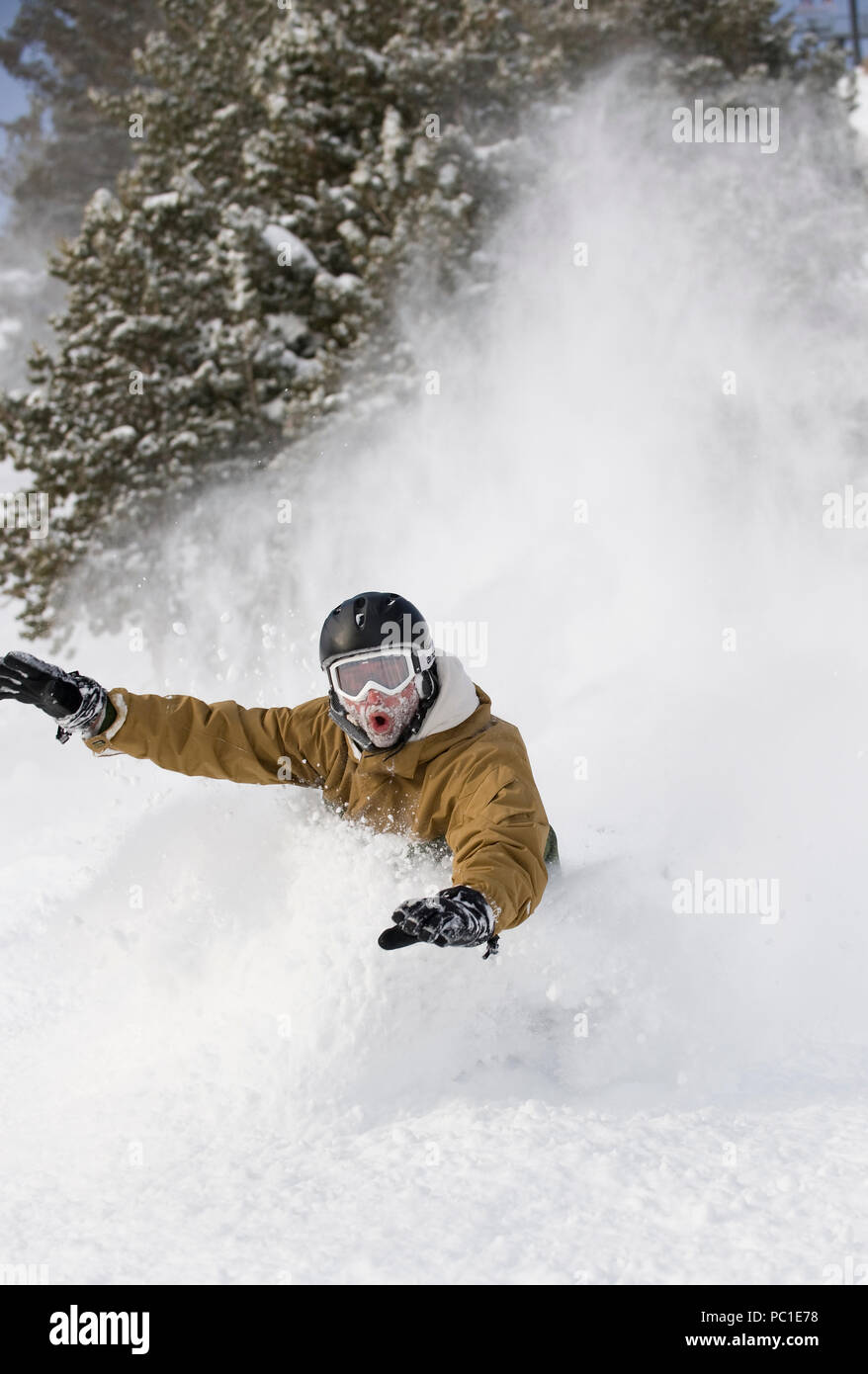 Happy snowboarder riding untracks fresh powder snow closeup. Stock Photo