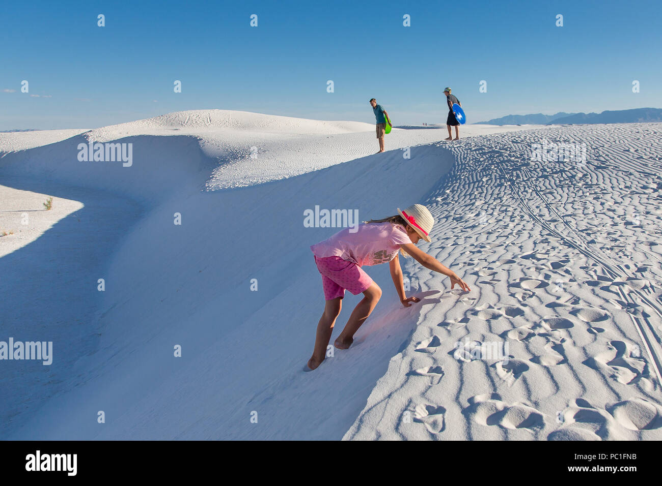 A girl climbs a white sand dune with her family in the background. - Stock Image