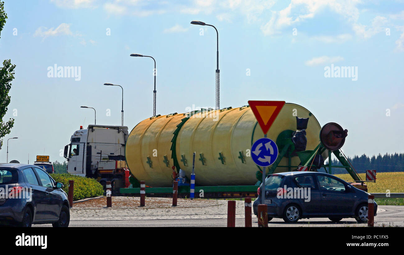Oversize load transport by semi trailer of Peter-Star, Poland, drives carefully through a narrow roundabout. Salo, Finland - July 27, 2018. - Stock Image