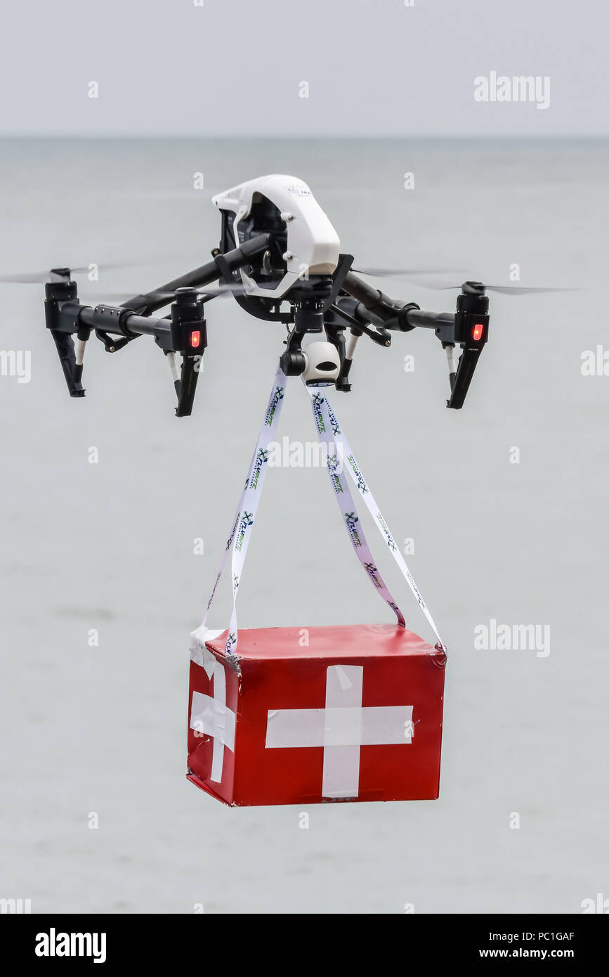 A DJI Inspire drone demonstrates how it can deliver a box of first aid supplies to a remote site quickly. - Stock Image