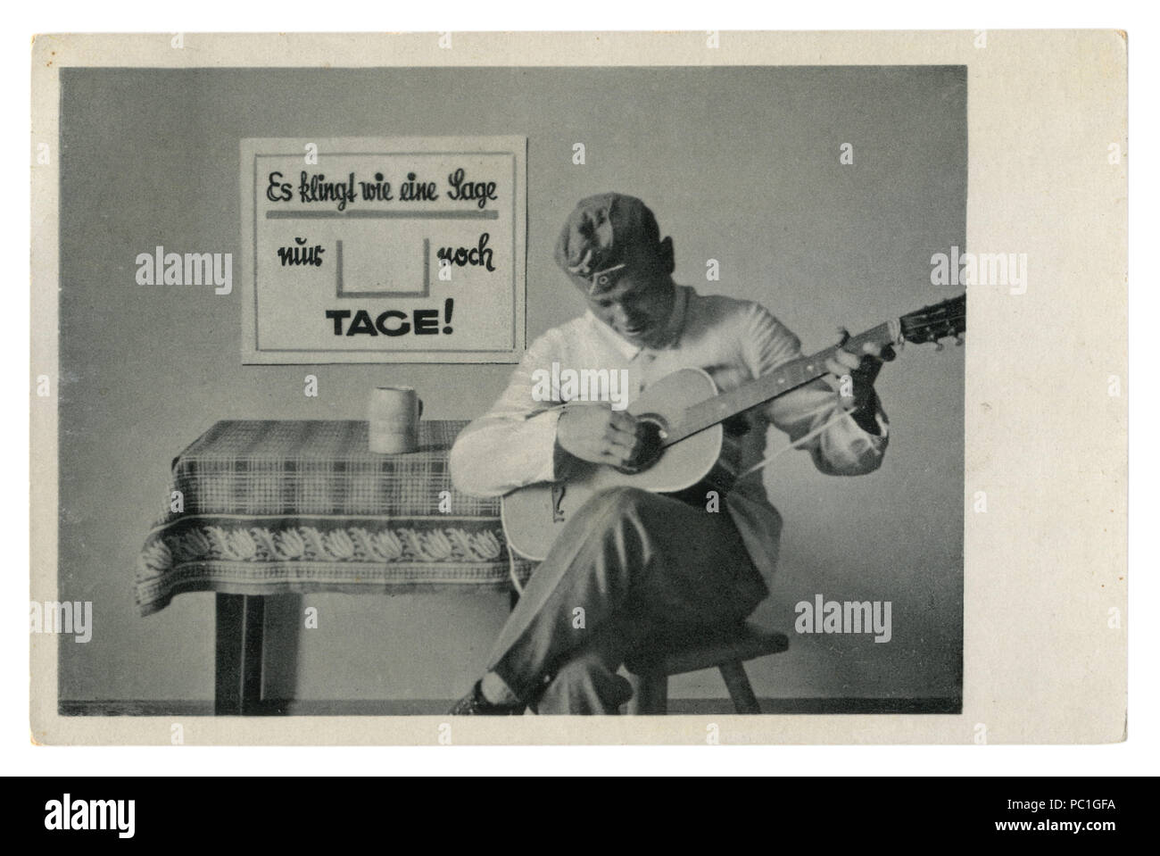 German historical photo postcard: soldier in forage cap plays guitar sitting on a chair. The army's leisure, world war two, Germany, Third Reich Stock Photo