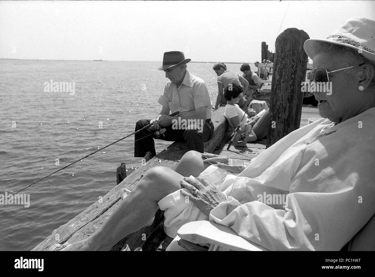 People relaxing and fishing on pier in Bridgeport, CT, 1982 Stock Photo