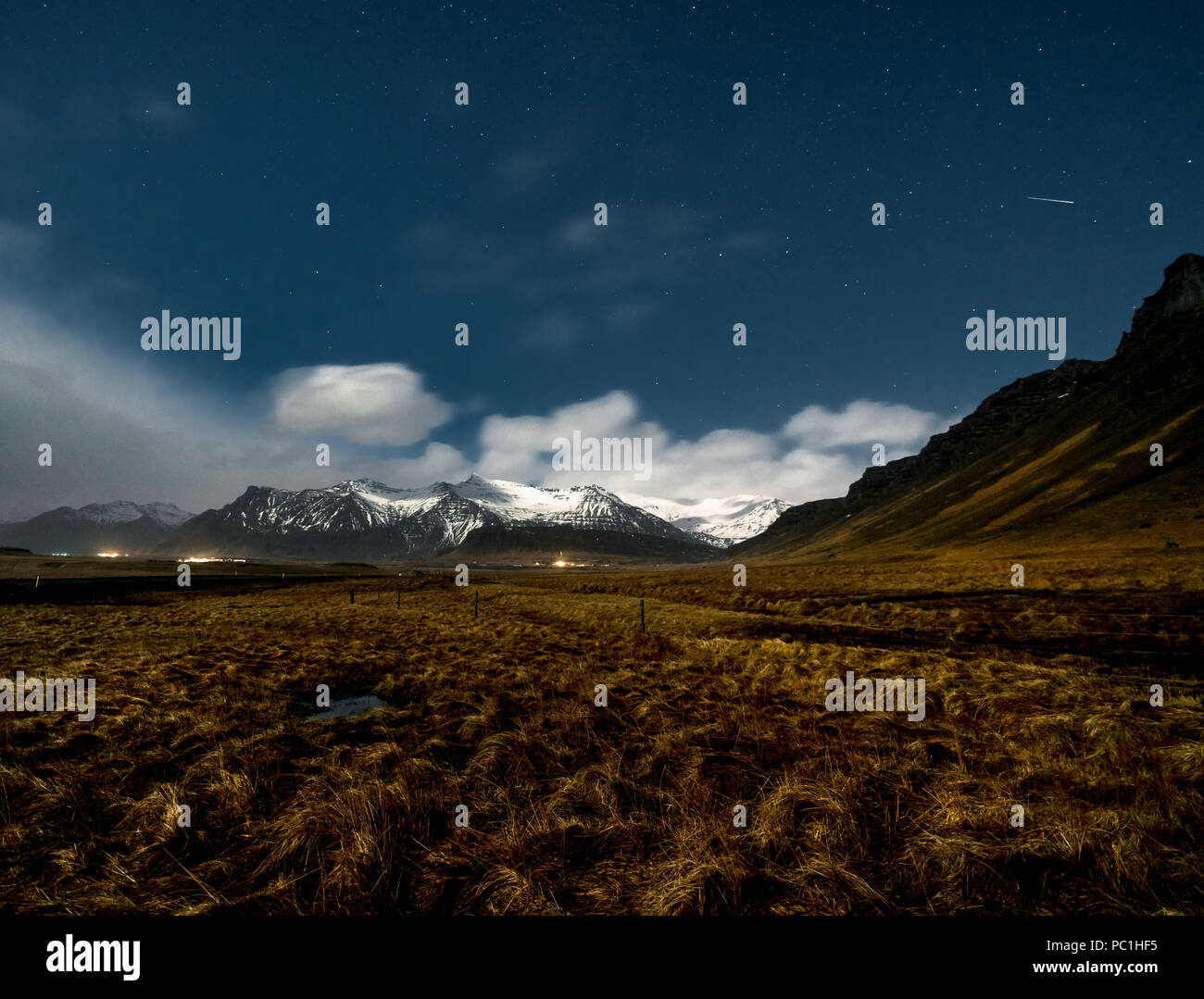 Night View Iceland with grass and blue sky stars with clouds and with view towards mountain. Southern side if the country. - Stock Image