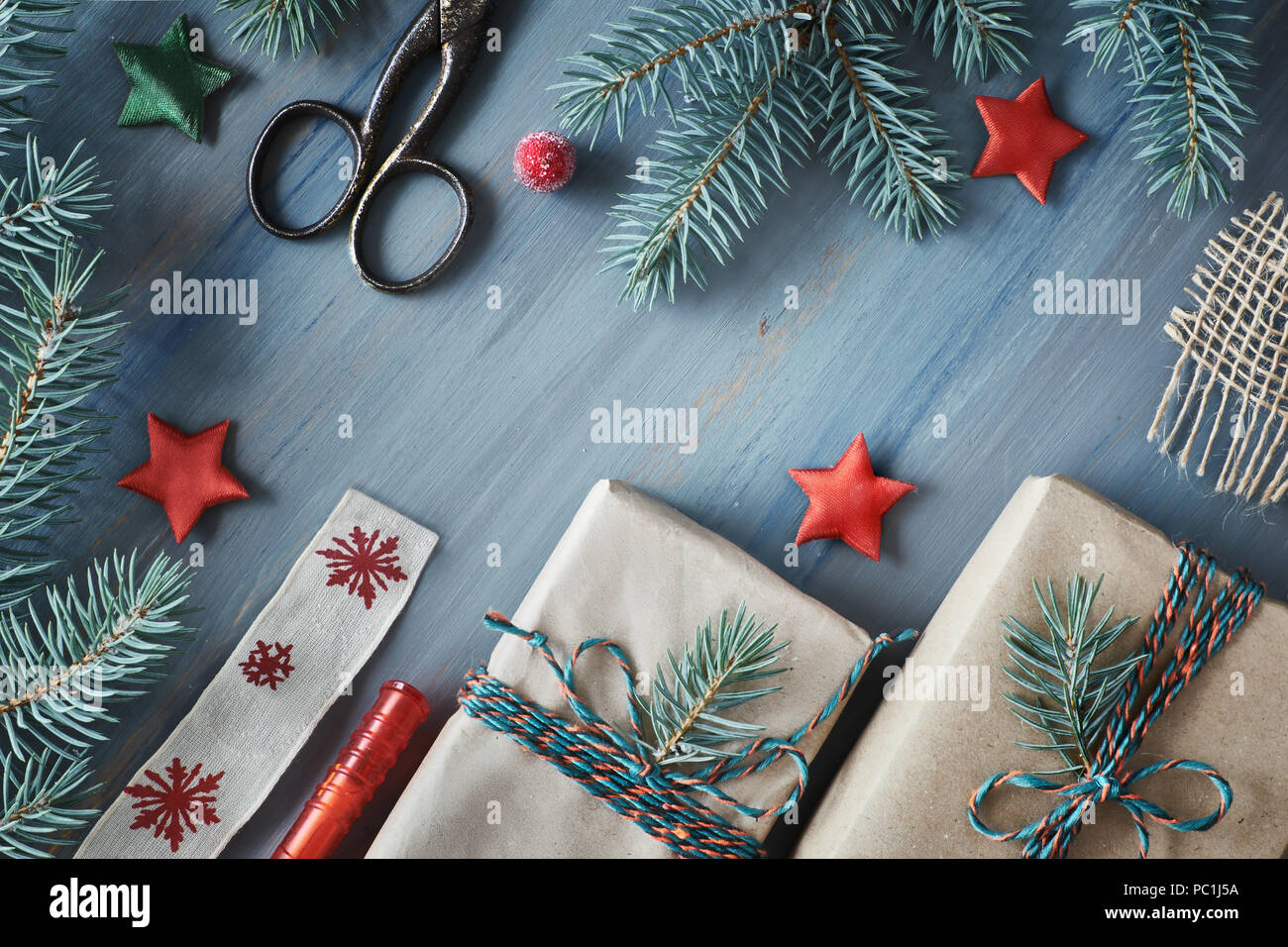 rustic wooden background in green and red with fir branches and christmas gifts in simple brown wrapping paper seasonal background shot from above f - Simple Christmas Gifts