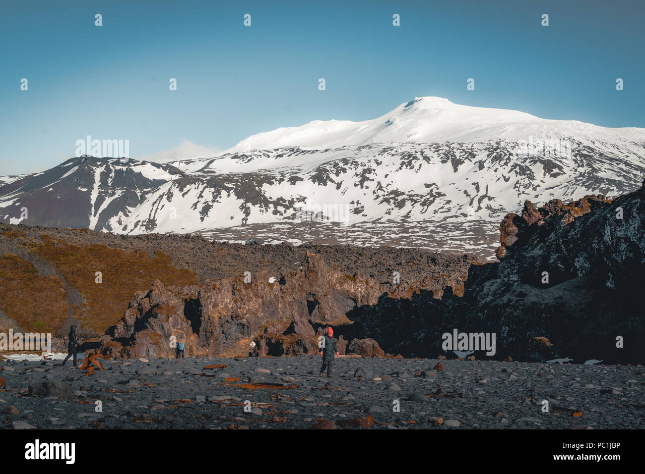 Iceland Black Beach Sand with snaefellsnesjokull mountain snow blue sky in Background. Western side if the country. - Stock Image