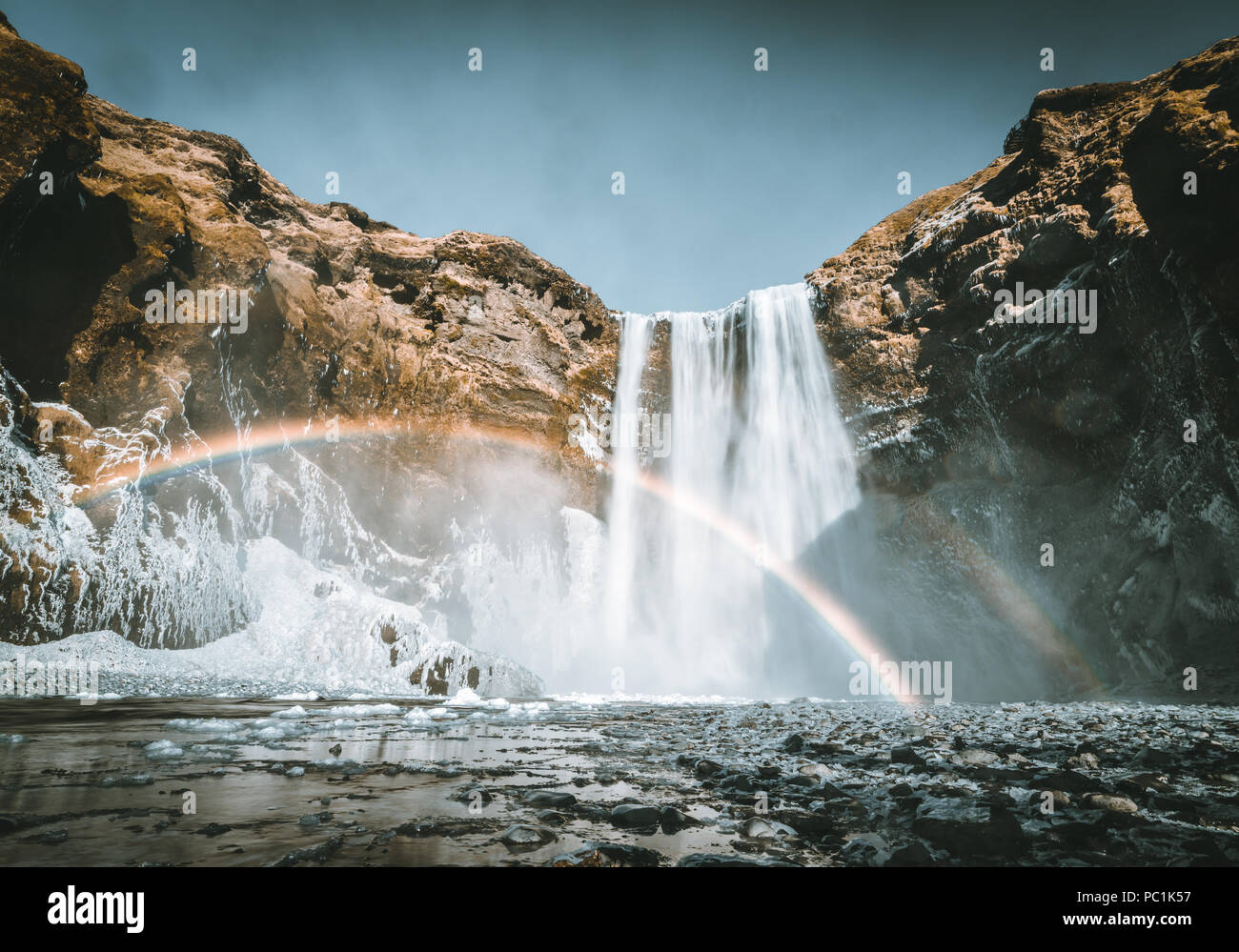 Skogafoss waterfall in Iceland with rainbow on a sunny day with blue sky. - Stock Image