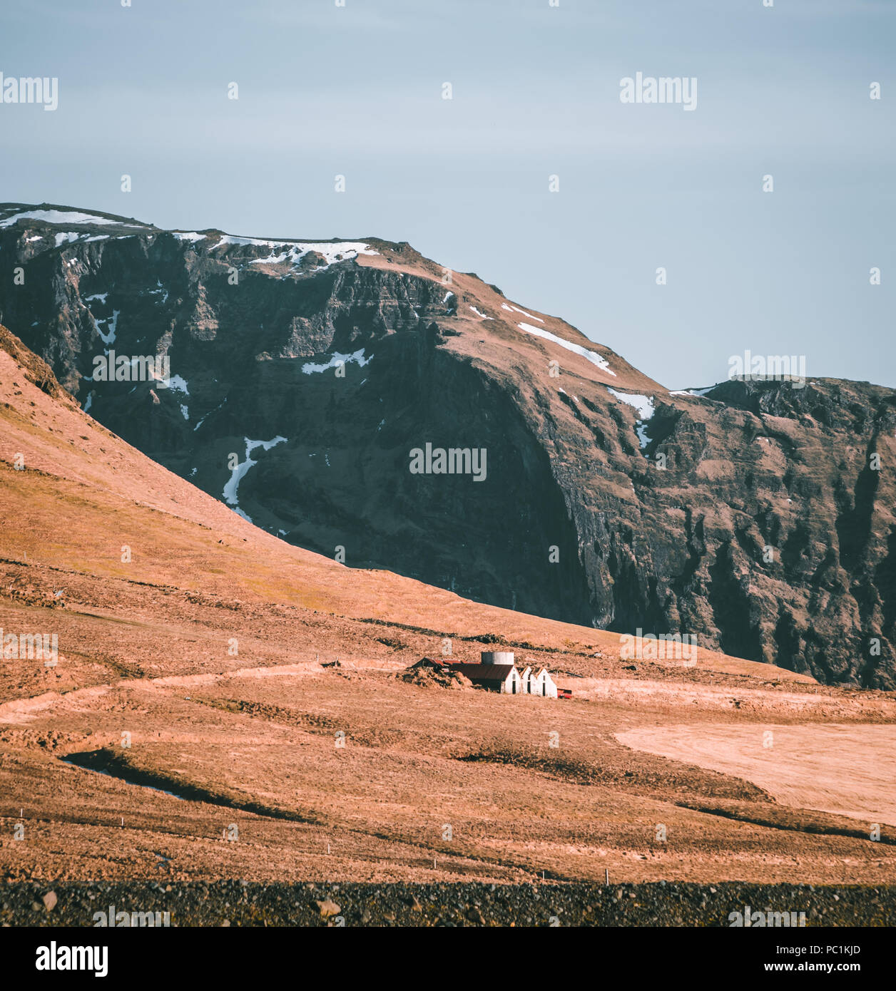 Typical Icelandic landscape with white houses red roof against mountains in small village in South Iceland. - Stock Image