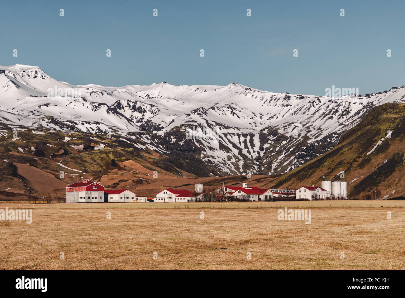 Typical Icelandic landscape with white houses red roof against mountains in small village in South Iceland. Stock Photo