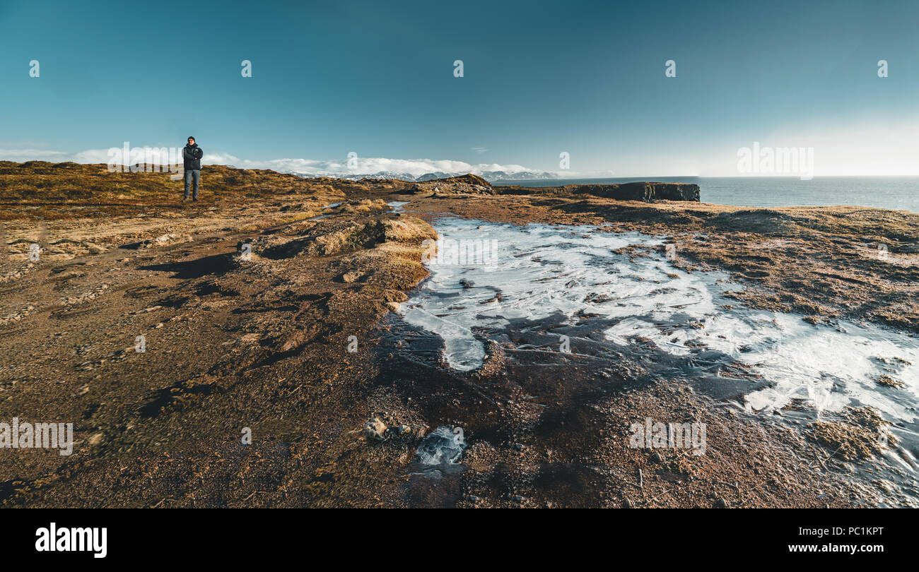 Arnarstapi , Iceland - May 2018: Young male tourist standing near a small icefield on a beautiful day with bue sky. - Stock Image