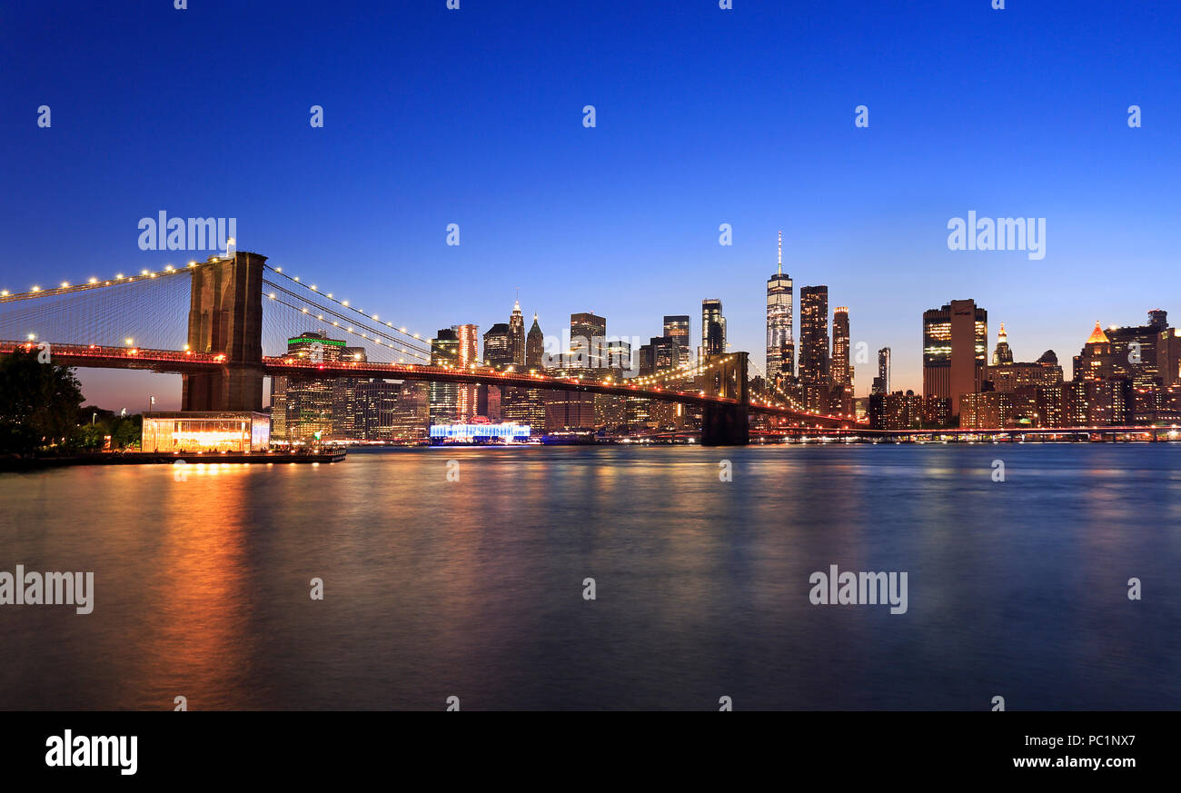 Panorama of Brooklyn Bridge and New York City (Lower Manhattan) with lights and reflections at dusk, USA - Stock Image