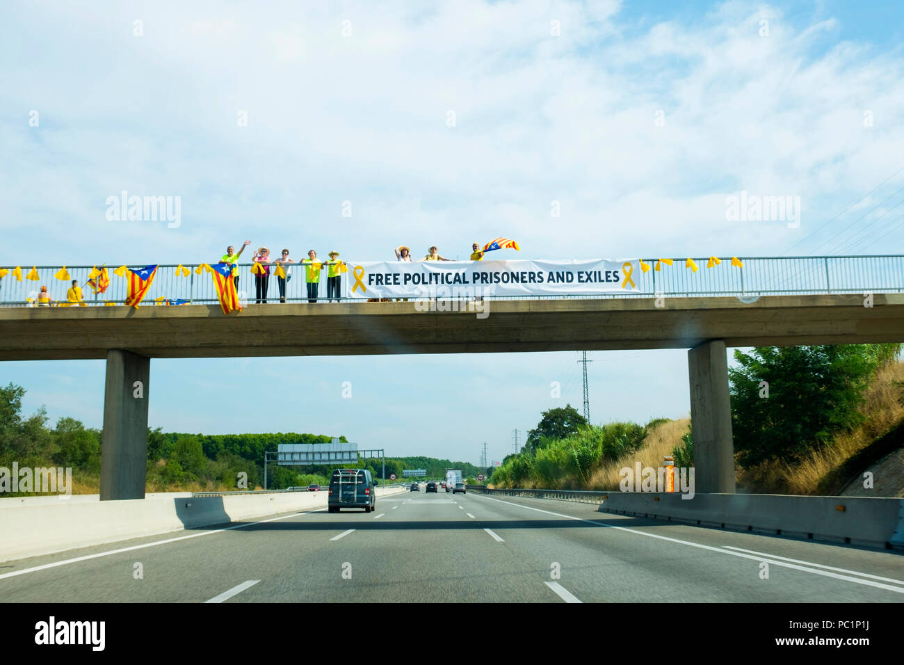 Pro-Catalan independence activists on flyovers used banners and flags to pronounce the Catalan republic and call for the release of political prisoner - Stock Image