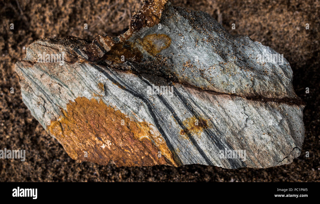 Geological metamorphic Rock with planes of fault undergoing rock erosion formed off Basalt of volcanic activity found in Konkan coast of Goa, India - Stock Image