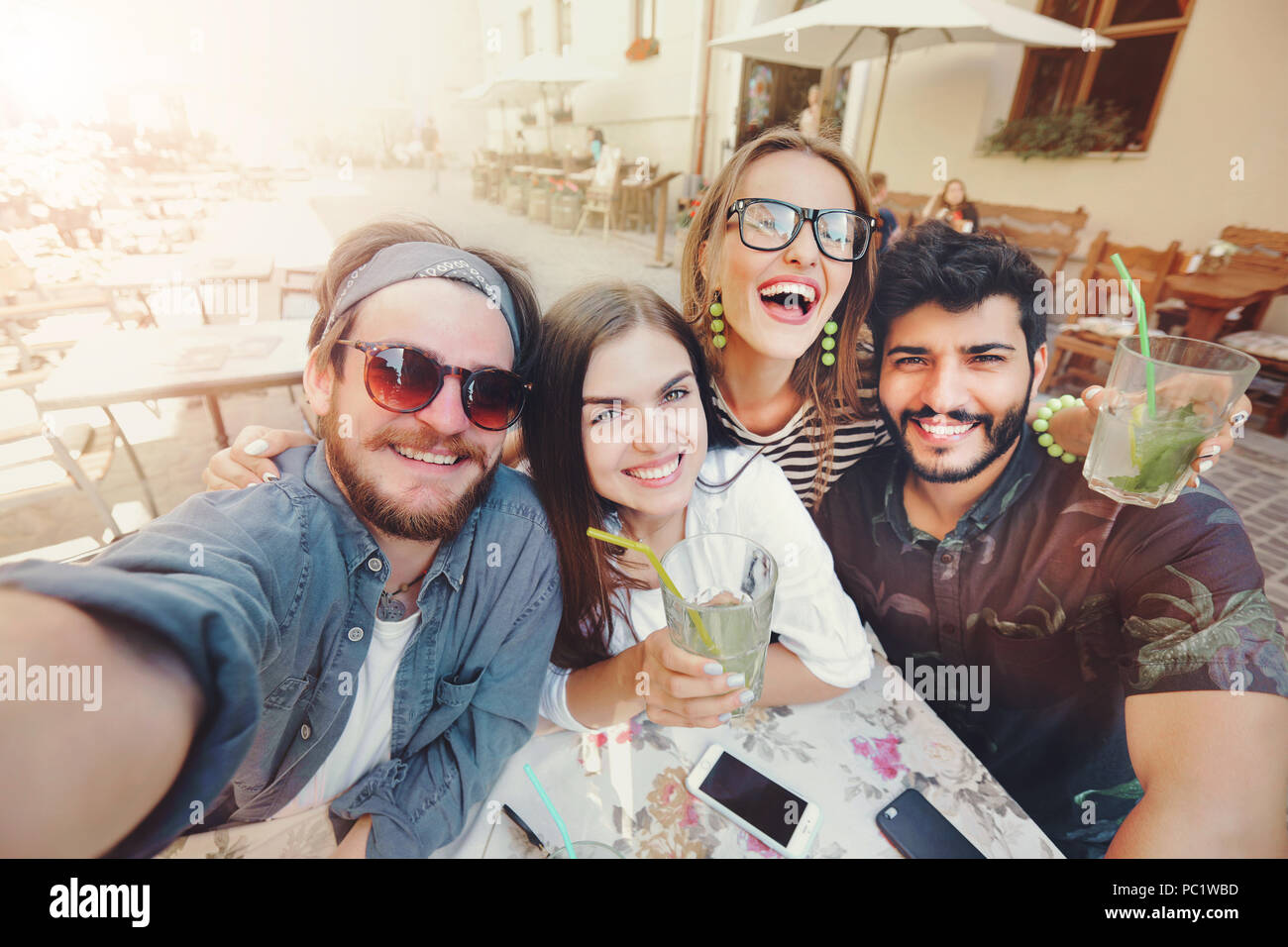 Four joyful cheerful friends taking a selfie while sitting together at cafe and showing mohito outdoors - Stock Image