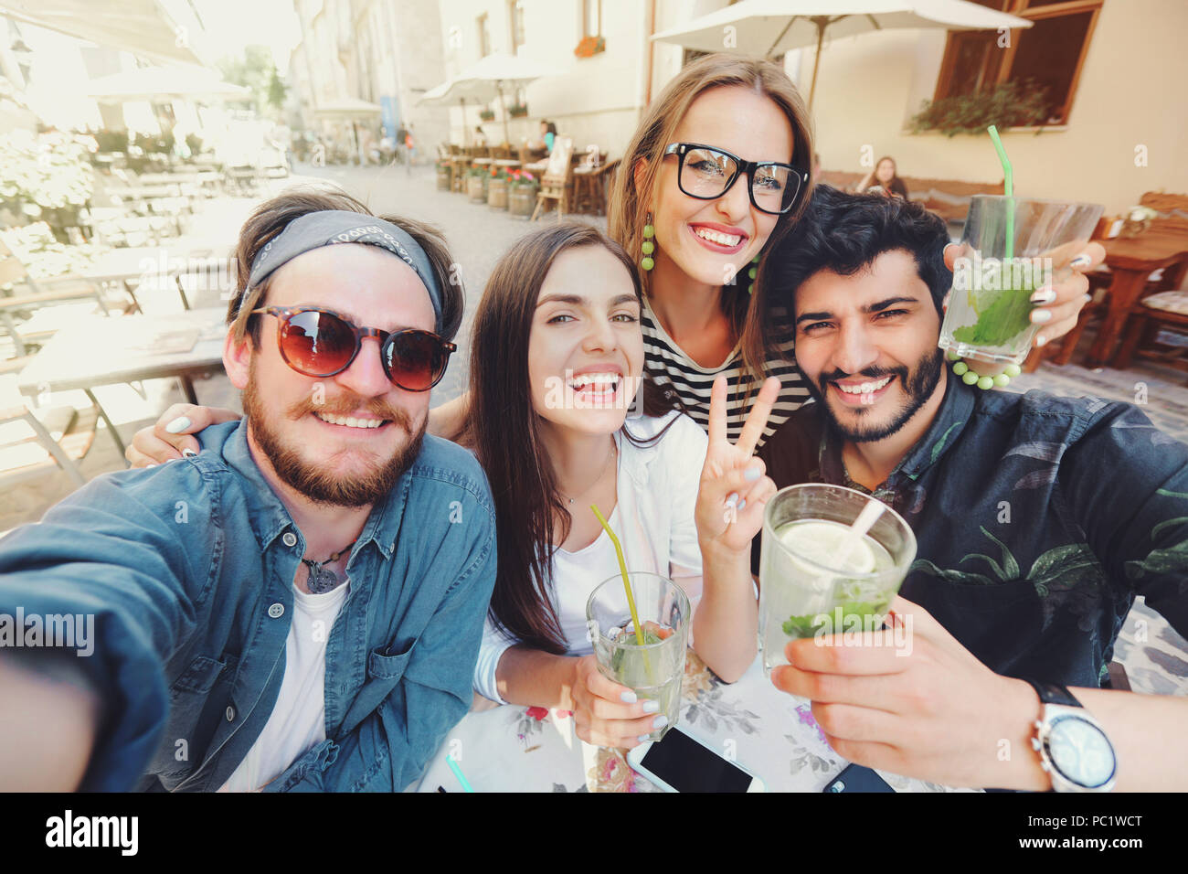 Four joyful cheerful friends taking a selfie while sitting together at cafe and showing peace gesture outdoors - Stock Image