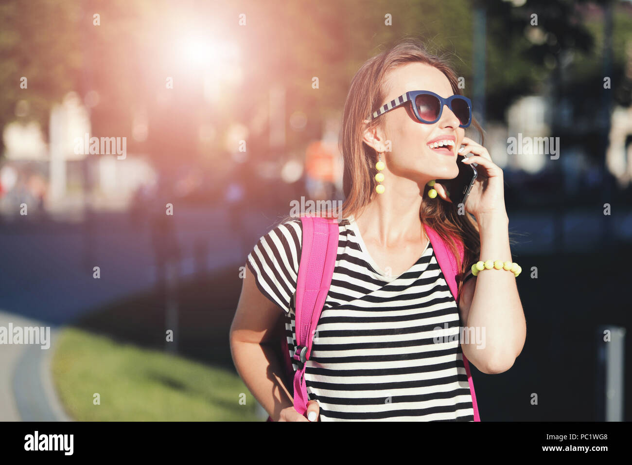 Cute stylish girl in sunglasses speaking on smartphone and walking with pink backpack at the summer street - Stock Image