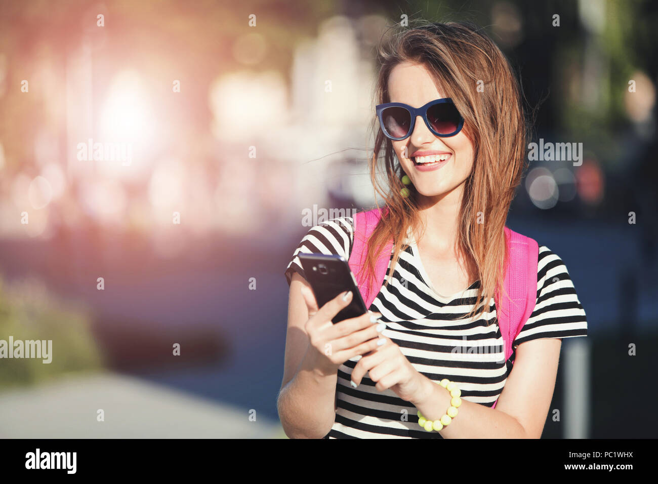 Young cute hipster girl in blue sunglasses taking selfie and walking with pink backpack at the summer street - Stock Image