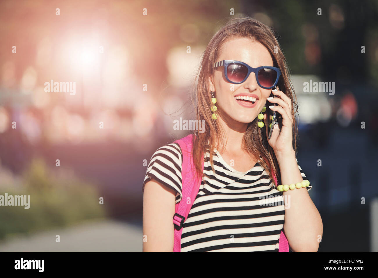 Young cheerful hipster girl in blue sunglasses calling on smartphone and walking with pink backpack at the summer street - Stock Image