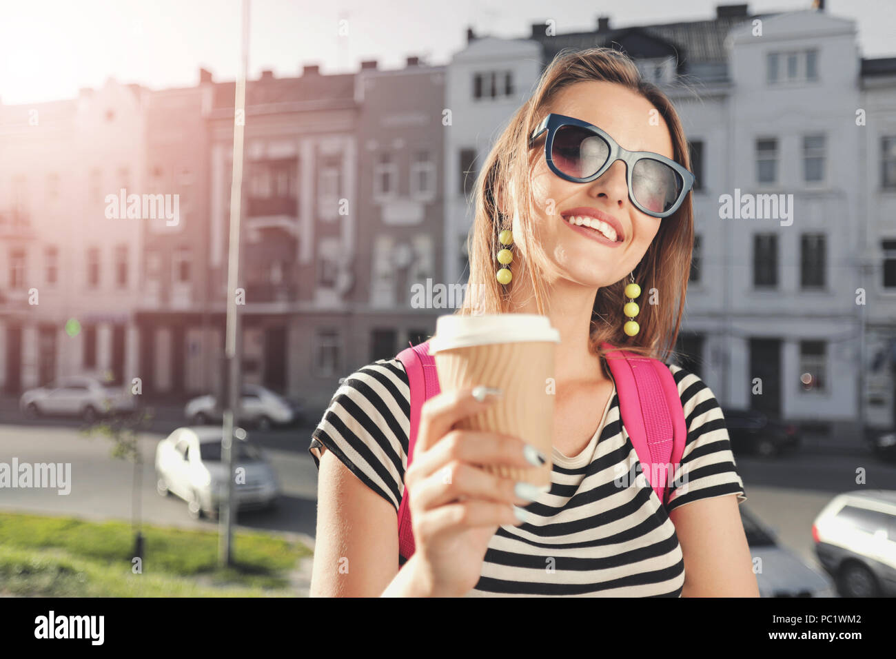 3e7c16f8db85 Pretty teenager long-hair girl in sunglasses drinking coffee and walking on  the street with pink backpack