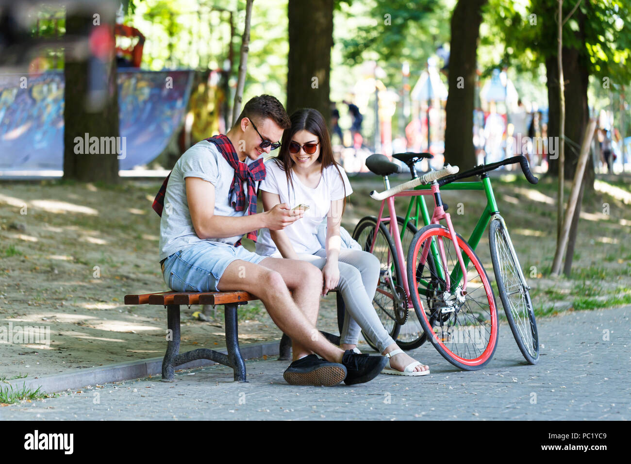 Young couple in love with bicycle sitting on beanch and looking something in the smartphone in the sunny summer park - Stock Image