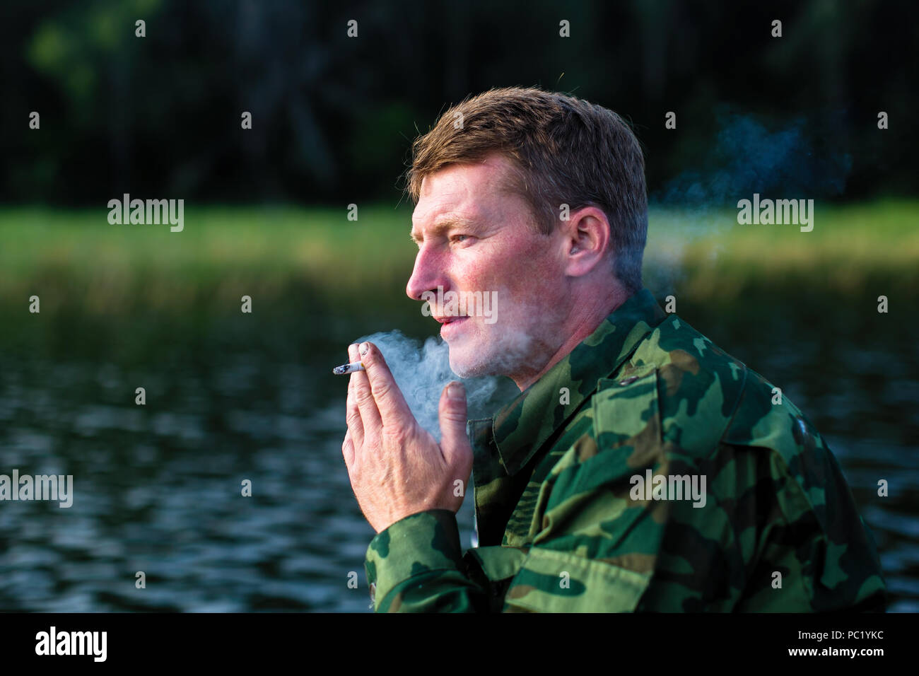 Man smoking close-up, camouflage clothing, outdoor. - Stock Image