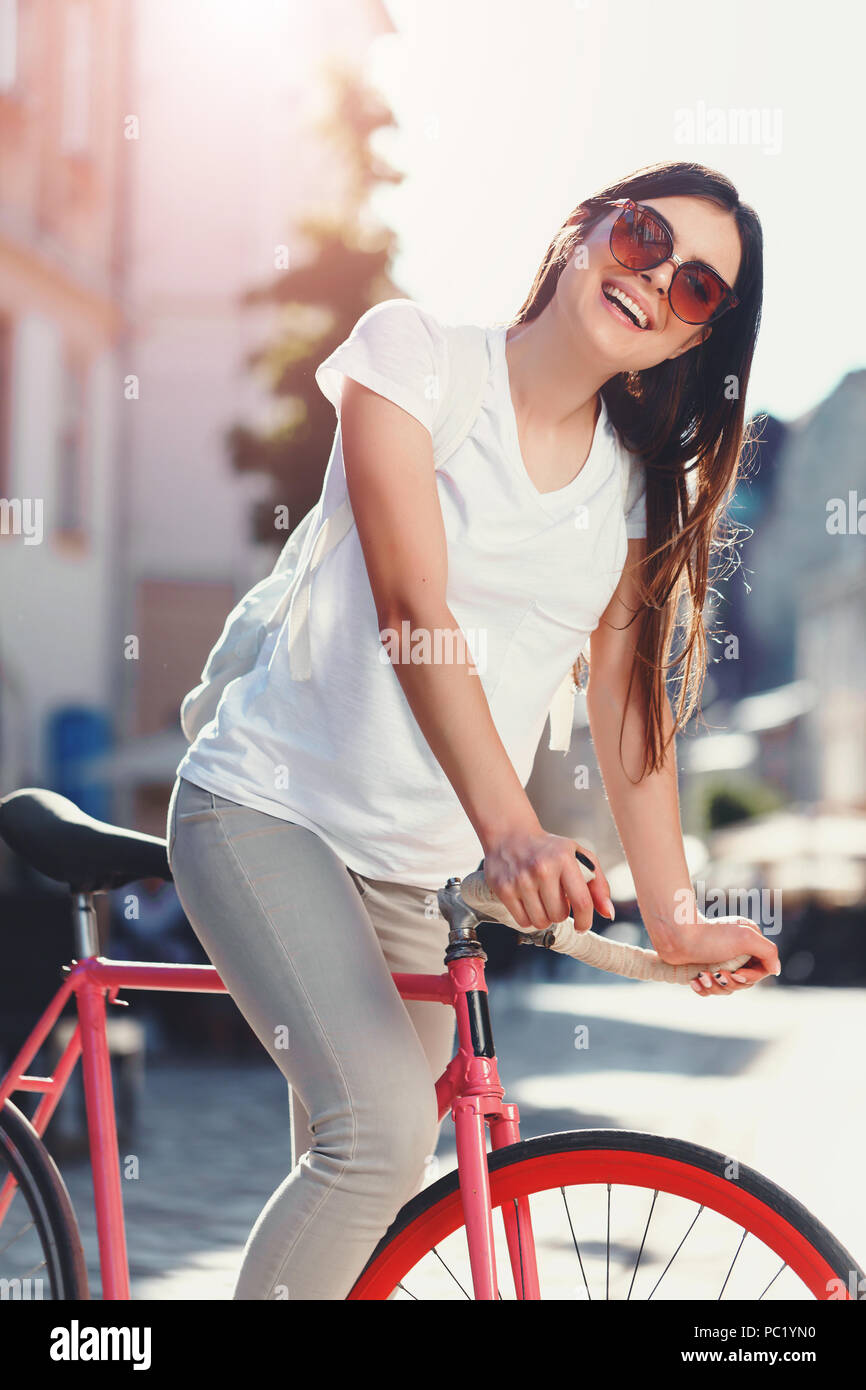 Portrait of young stylish hipster romantic long-hair girl in sunglasses staying with pink bicycle and laughing at sunny summer street - Stock Image