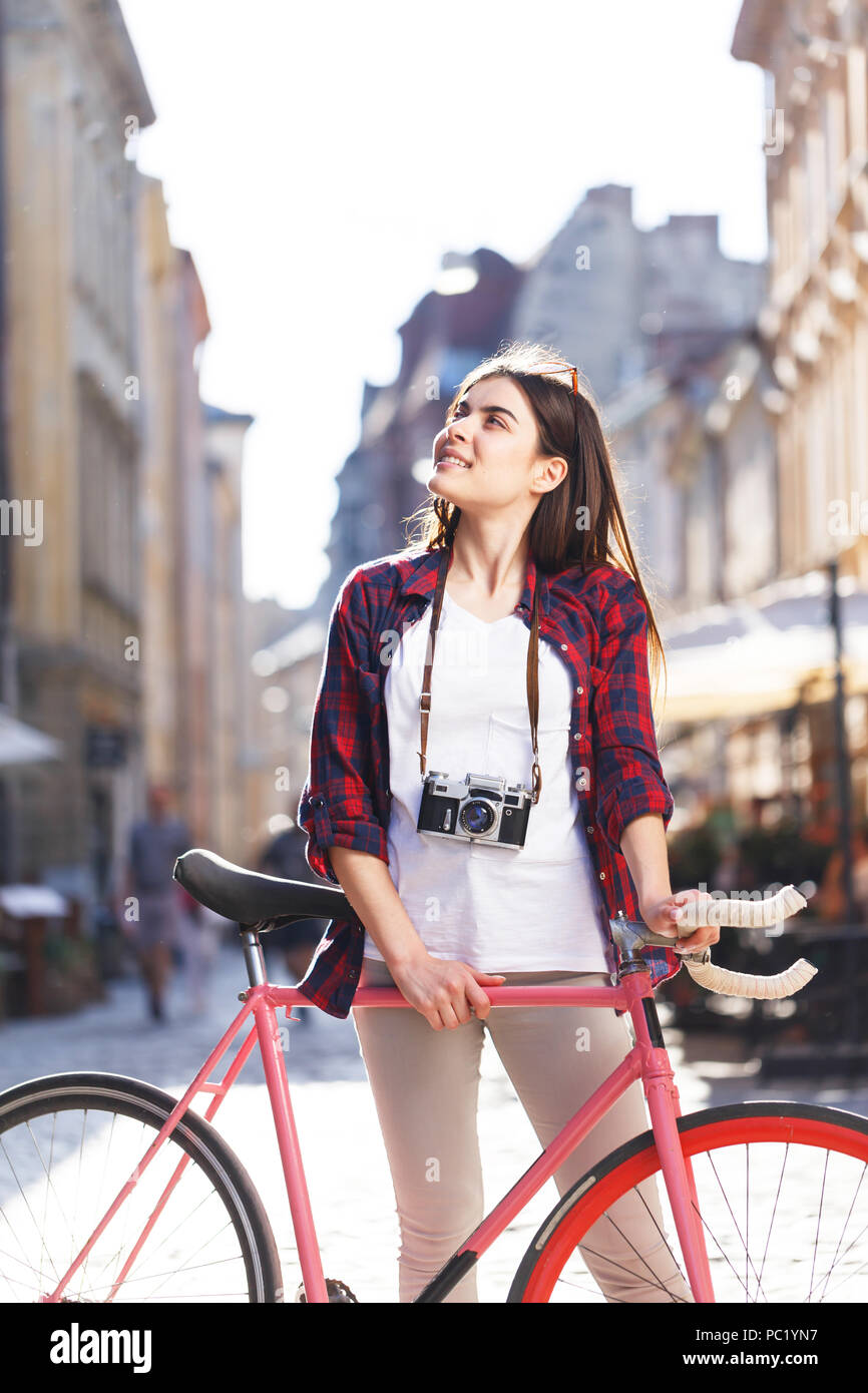 Young stylish hipster cute long-hair girl in sunglasses staying with pink bicycle and looking on the views at sunny summer street - Stock Image