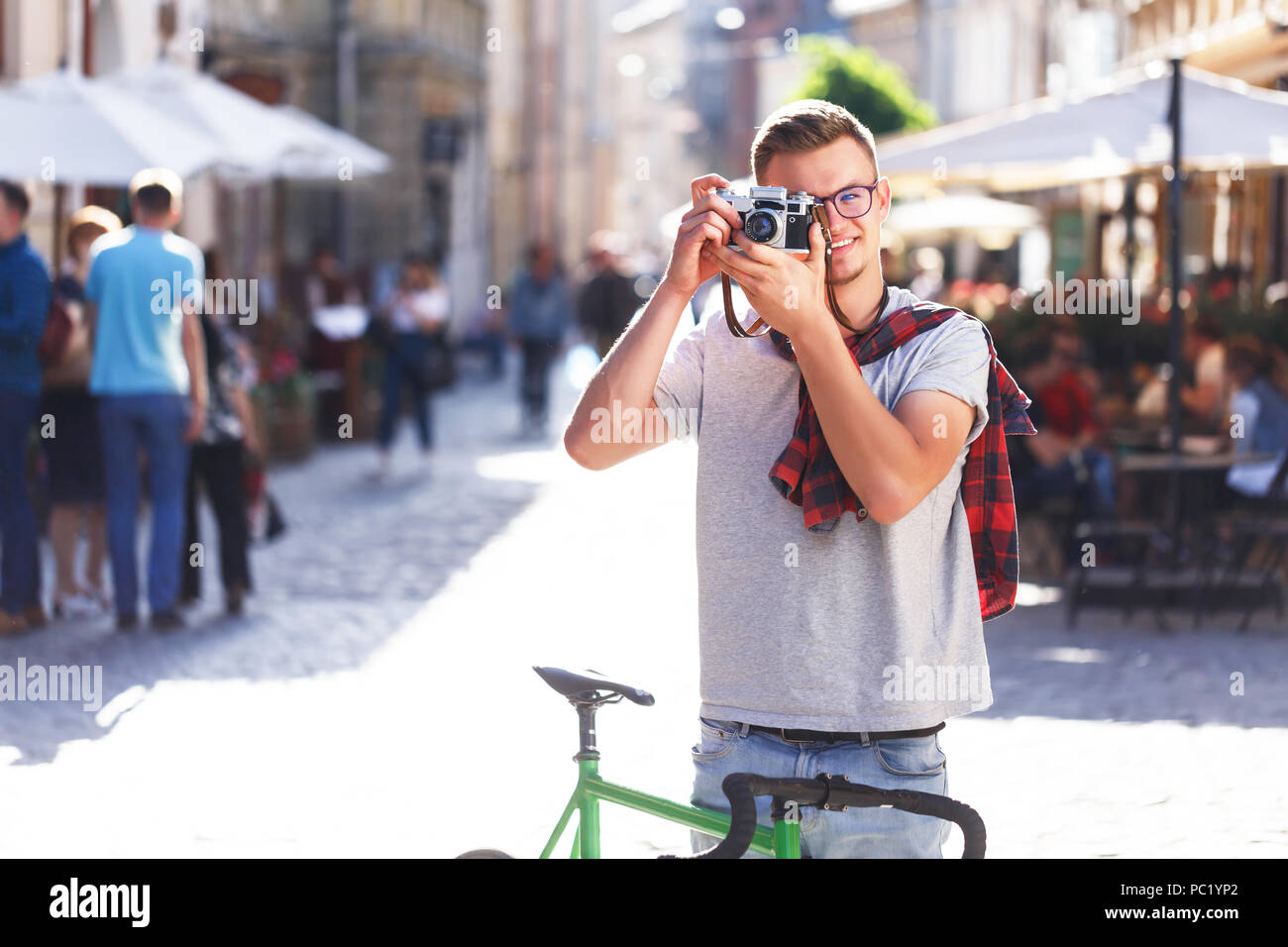 Portrait of young hipster light-hair boy in glasses staying with green bicycle and making photo at sunny summer street - Stock Image