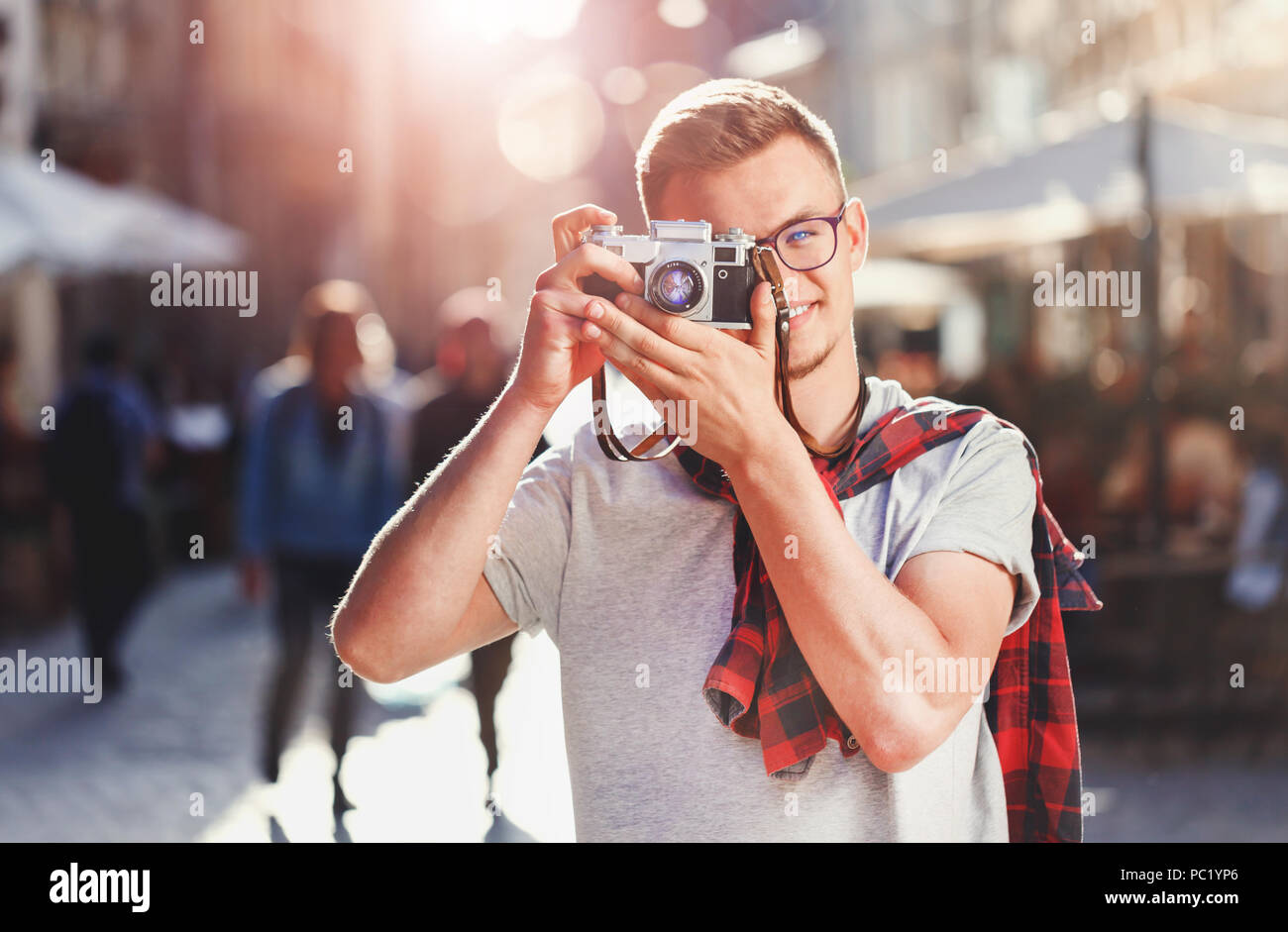 Portrait of young hipster light-hair boy in glasses staying with green bicycle and making photo of amazing views at sunny summer street - Stock Image